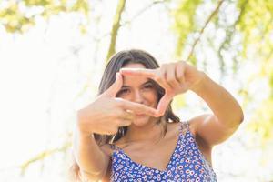 linda morena fazendo moldura com os dedos foto