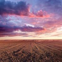 terra cultivada e formações de nuvens ao pôr do sol