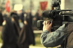 um homem com uma grande câmera de vídeo foto