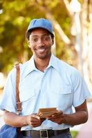 carteiro caminhando pela rua entregando cartas
