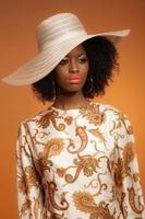 anos 70 retrô moda mulher afro com vestido estampado e chapéu.
