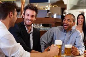 jovens empresários bebendo cerveja em bar foto
