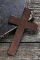 cruz e livro velho na mesa de madeira
