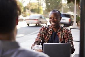 dois amigos do sexo masculino com bebidas geladas e laptop fora do café