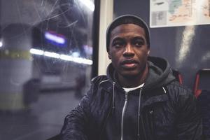 homem afro com boné de lã, sentado à janela do metrô. foto