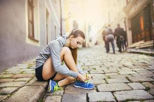 jovem corredora amarrando os sapatos foto