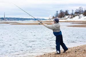 menino pescando girando na margem do rio foto