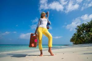 linda garota com uma mala vintage em uma praia