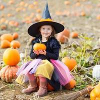 menina usando fantasia de bruxa de halloween em uma plantação de abóboras