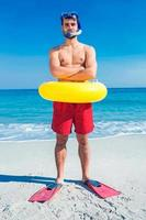 homem usando nadadeiras e anel de borracha na praia foto