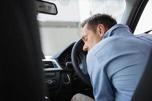 um homem bêbado desmaiado em um volante foto