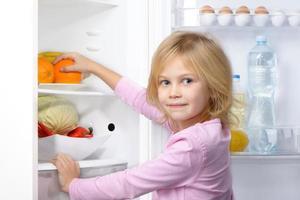 menina olhando para a câmera e pegando comida na geladeira