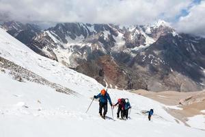 grupo de caminhantes caminhando em terreno de neve e gelo foto