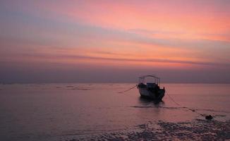 céu laranja, mares cinzentos e um barco solitário