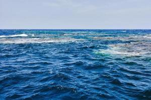superfície do mar vermelho, recife de coral e céu foto