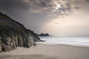 praia de areia amarela de porthcurno antes do pôr do sol