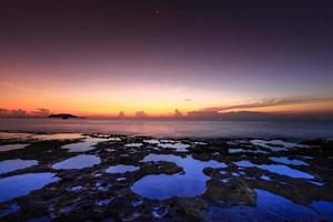 rochas vulcânicas na costa ao amanhecer foto