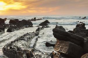 Praia Barrika ao pôr do sol. longa exposição na costa rochosa foto