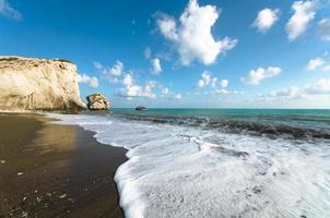 oceano turquesa e céu azul com penhasco rochoso ao fundo