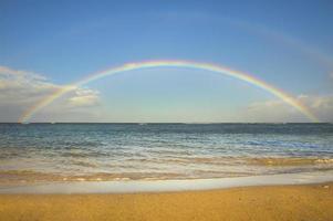 arco-íris duplo sobre o oceano na praia foto