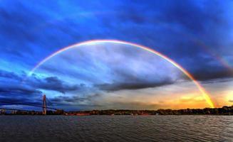 arco-íris do pôr do sol à beira do rio foto