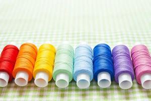 fila de carretéis de linha nas cores do arco-íris foto