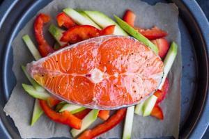 cozinhando bife cru de peixe vermelho, salmão em vegetais, abobrinha