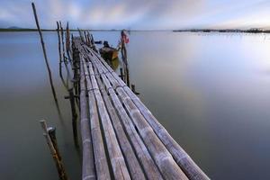 ponte de bambu que se estende até o mar.