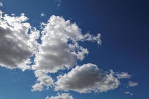 céu azul com nuvens cúmulos brancas.