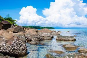 bela praia tropical com pedras coloridas e águas azuis