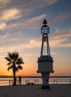 ayamonte, andaluzia, espanha, pôr do sol com palmeira e estrutura marítima