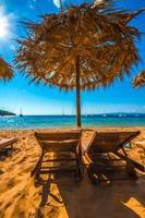 guarda-sol de palmeira com cadeira de praia foto