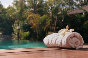 toalha branca perto da piscina com palmeiras