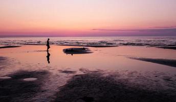 pôr do sol na praia e a silhueta do homem, jurmala
