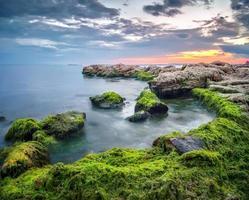 paisagem de verão ao nascer do sol com pedras, musgo e um céu incrível foto