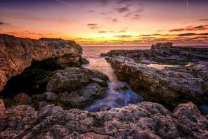 lindo nascer do sol dramático na praia rochosa