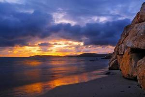 rochas e areia na costa de alghero ao pôr do sol