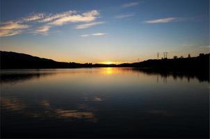 pôr do sol azul e laranja. reflexão no reservatório