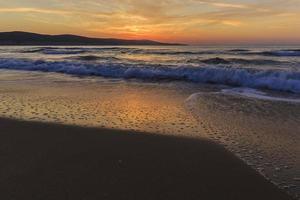 nascer do sol na costa de uma praia ensolarada na bulgária foto