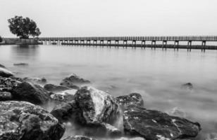 foto em preto e branco da ponte de madeira ao longo da praia