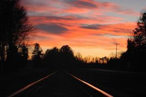 reflexos do pôr do sol nos trilhos da ferrovia foto