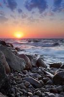 a praia de seixos ao pôr do sol - rozewie, polônia, longa exposição