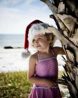 menina com chapéu de Papai Noel na praia