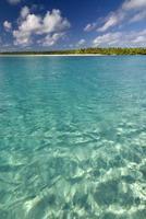 água tropical arenosa e rasa com uma ilha de palmeiras à distância