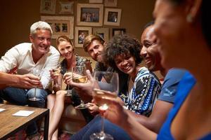 grupo de amigos sentados ao redor de uma mesa em uma festa em casa foto