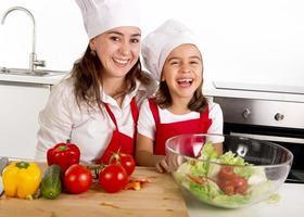 mulher e filha preparando salada na cozinha de casa foto