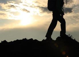silhueta de mochileiro caminhando no pico da montanha ao pôr do sol
