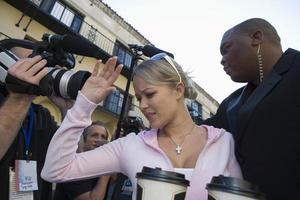 celebridade com guarda-costas e paparazzi foto