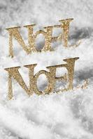 palavras brilhantes de noel de ouro na neve branca foto