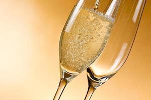 taças vazias de champanhe e uma sendo enchida foto